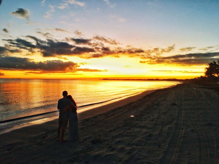 Silhouette Couple Embracing While Standing At Beach Against Sky During Sunset