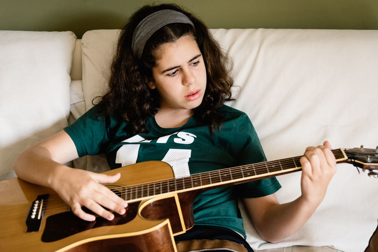 Teenage girl playing guitar while sitting on sofa at home