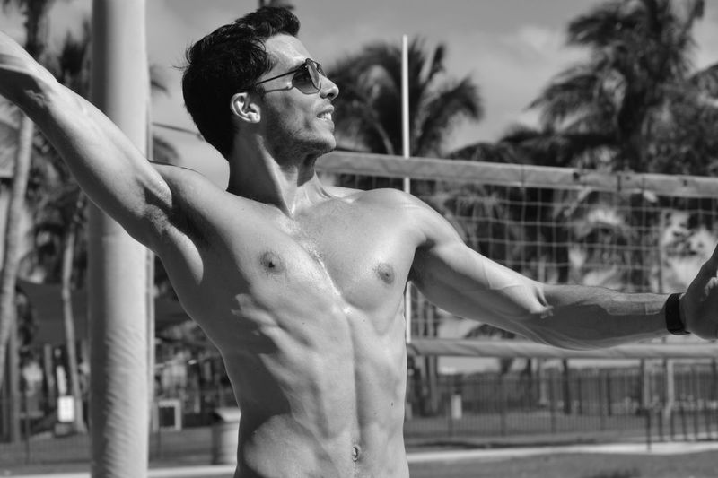 Muscular man with arms raised standing at beach
