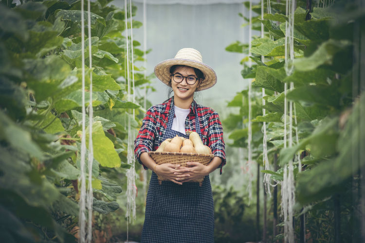 Portrait of a smiling young woman holding food outdoors