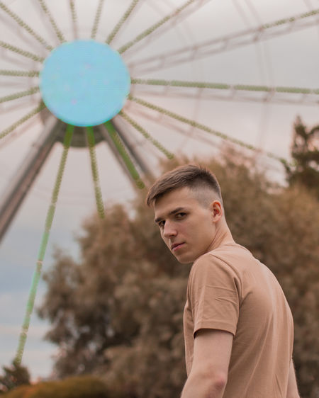 Portrait of young man standing in amusement part ride