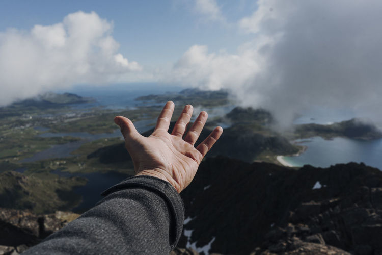 Cropped hand of person over mountains against sky