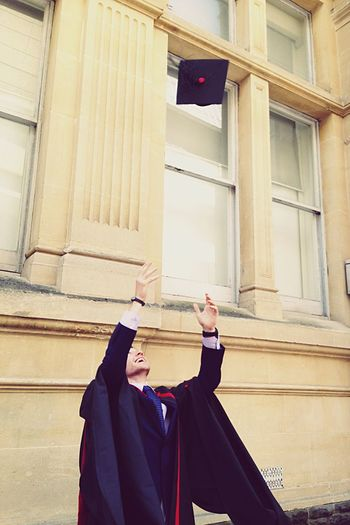 Graduate Tossing Cap Against University Building