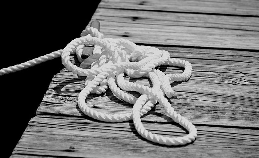 Curled rope on wooden pier in Topping, VA Curled Pier Rope Topping, VA Black And White Close-up Day Monochrome Nautical Vessel No People Rappahannock River Wood - Material Wooden