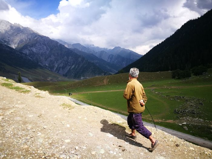 Rear view of man on mountains against sky