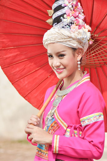Happy young woman wearing traditional clothing while holding paper umbrella