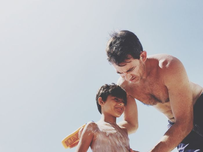 Low angle view of father and son against clear sky