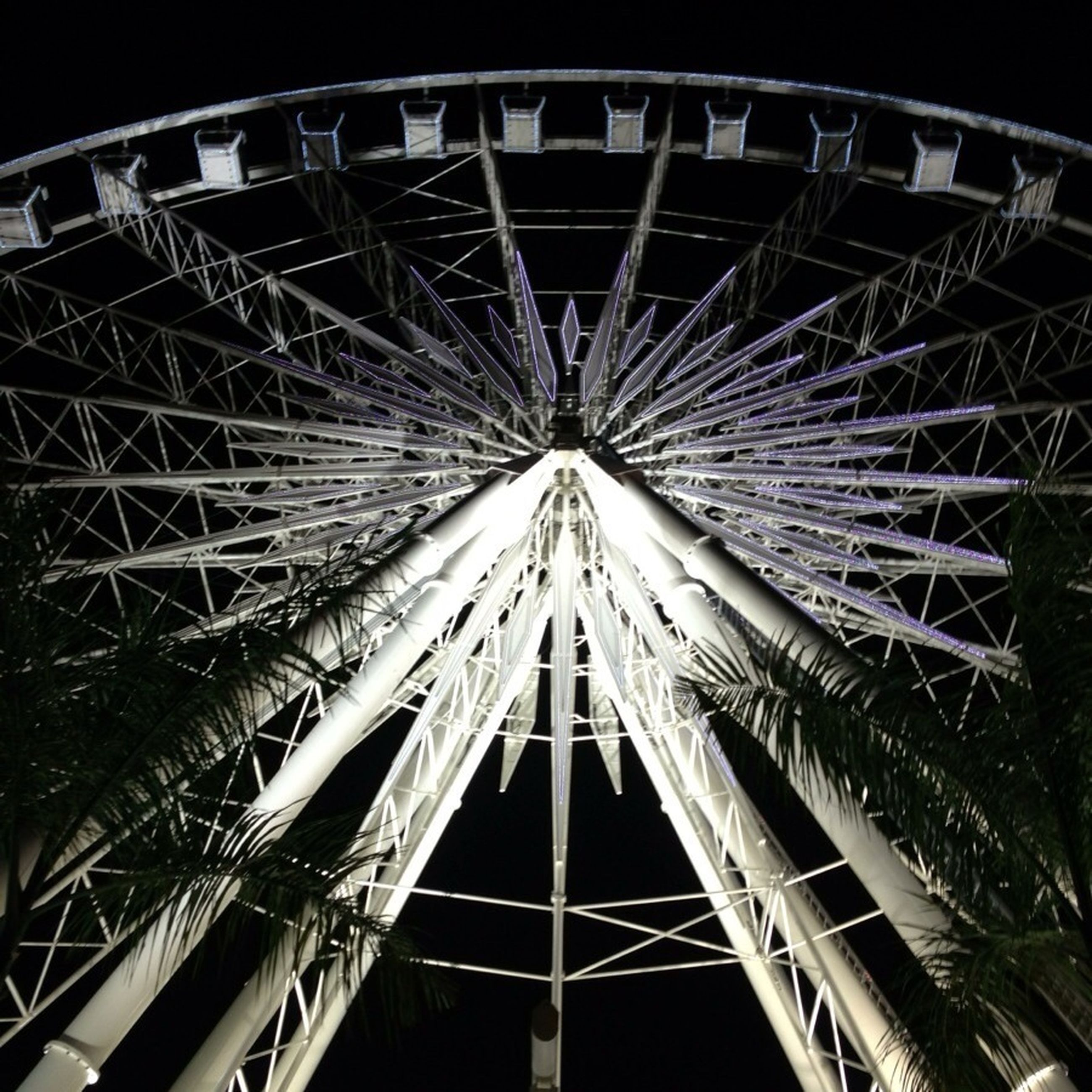 low angle view, built structure, architecture, arts culture and entertainment, night, ferris wheel, amusement park, metal, amusement park ride, sky, clear sky, illuminated, travel destinations, famous place, metallic, architectural feature, outdoors, no people, international landmark, engineering