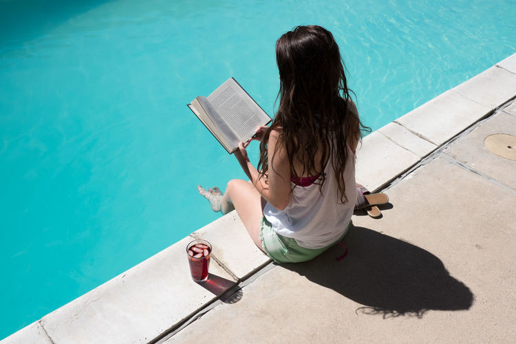 High angle view of woman reading book at poolside