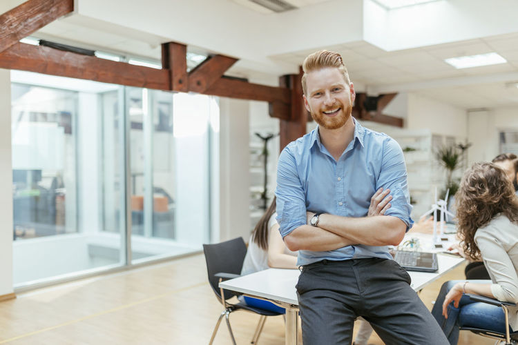 Portrait of a smiling young man sitting in office