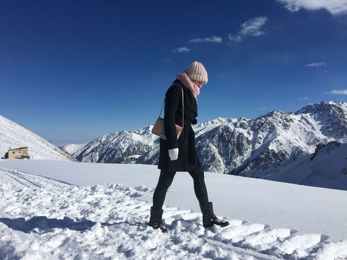 Side view of young woman walking on snowcapped mountain against blue sky