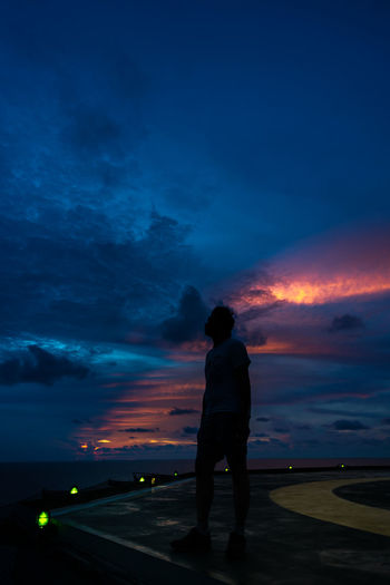 Rear view of silhouette man standing against sky at sunset
