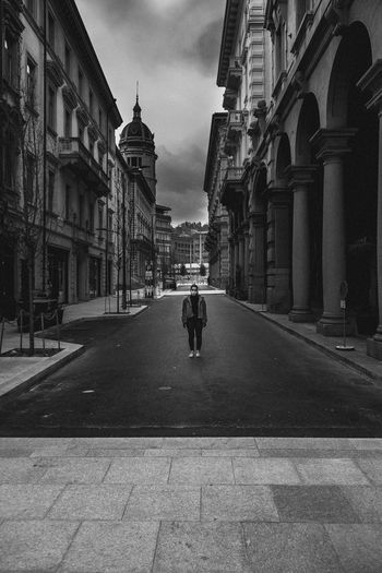 Woman standing on road amidst buildings in city