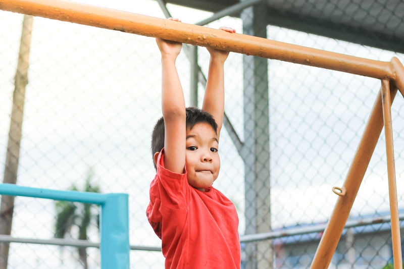 Boy hanging on metal in playground