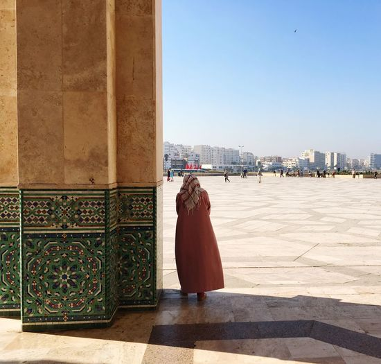 Rear view of woman standing at mosque against sky