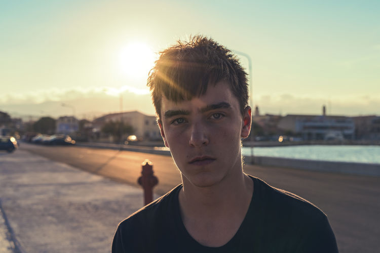 Portrait of young man standing in city against sky during sunset
