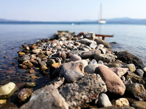 Beach Beauty In Nature Day Land Nature No People Outdoors Rock - Object Rocks Rocky Coastline Sailboat Sea Sea And Sky Sea Life Seaandsky Seaside Selective Focus Sky Solid Stone Stone - Object Stone Material Water