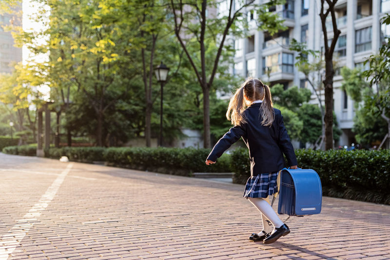 Girl holding backpack while walking on footpath