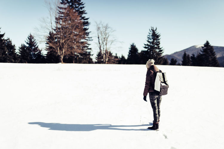 Full length of woman standing on snow covered landscape