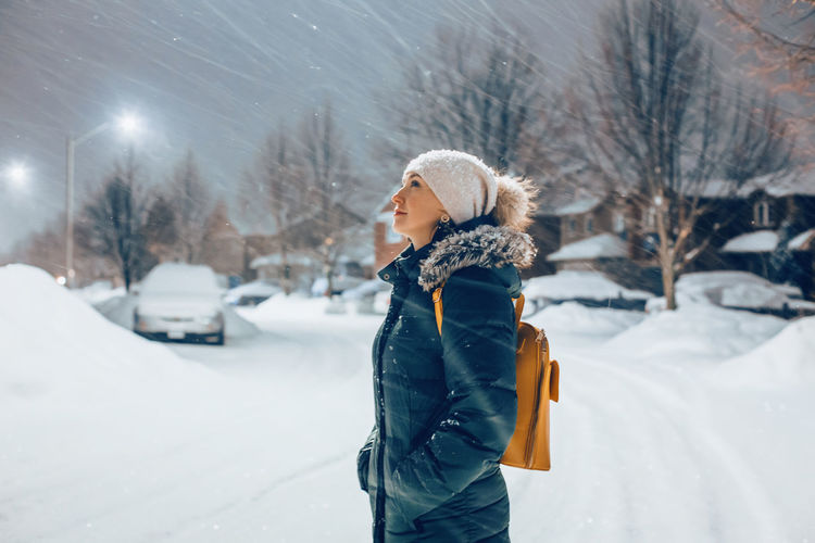 Woman in blue jacket winter clothes and hat walking outdoors under snow. winter romantic wonderland.