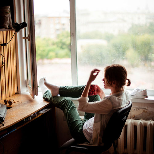 Woman Relaxing On Window