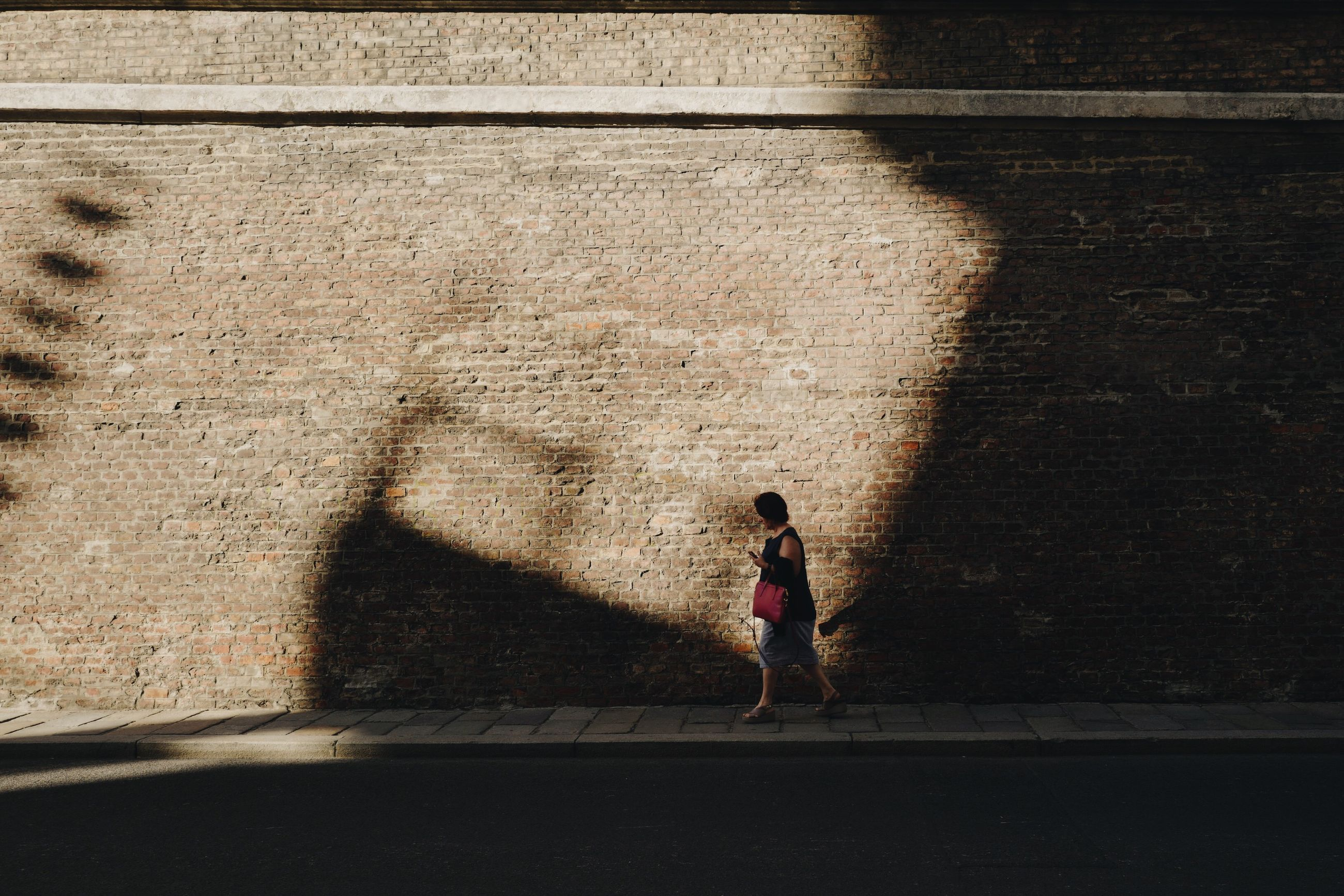 full length, shadow, one person, sunlight, real people, walking, architecture, wall - building feature, women, footpath, day, lifestyles, built structure, child, nature, wall, adult, sidewalk, city, outdoors