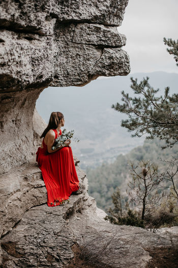 Rear view of woman walking on rock against trees