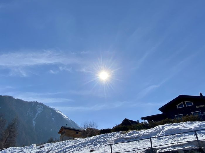 Sun shining over snow covered houses and mountains against sky