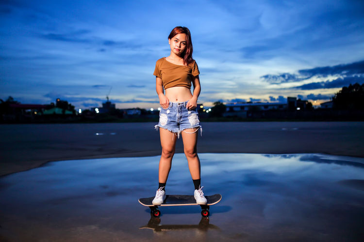 Asian women playing surf skate or skates board outdoors.