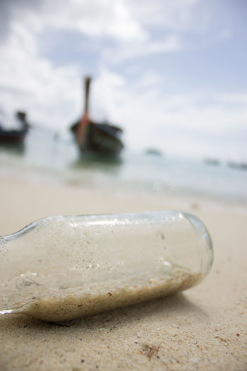 Sky & Sea Beach Beauty In Nature Bottle Close-up Cloud - Sky Day Focus On Foreground Land Nature Nautical Vessel No People Outdoors Pollution Sand Sea Selective Focus Shell Sky Surface Level Tranquility Water