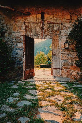 An old doorway, Italy. Ancient Building Doorway Dusk Golden Hour Grass Italian Building Light Light And Shadow Mammal Masonry Monastery Old Door Shadows Stones Vintage Building Weathered Wood