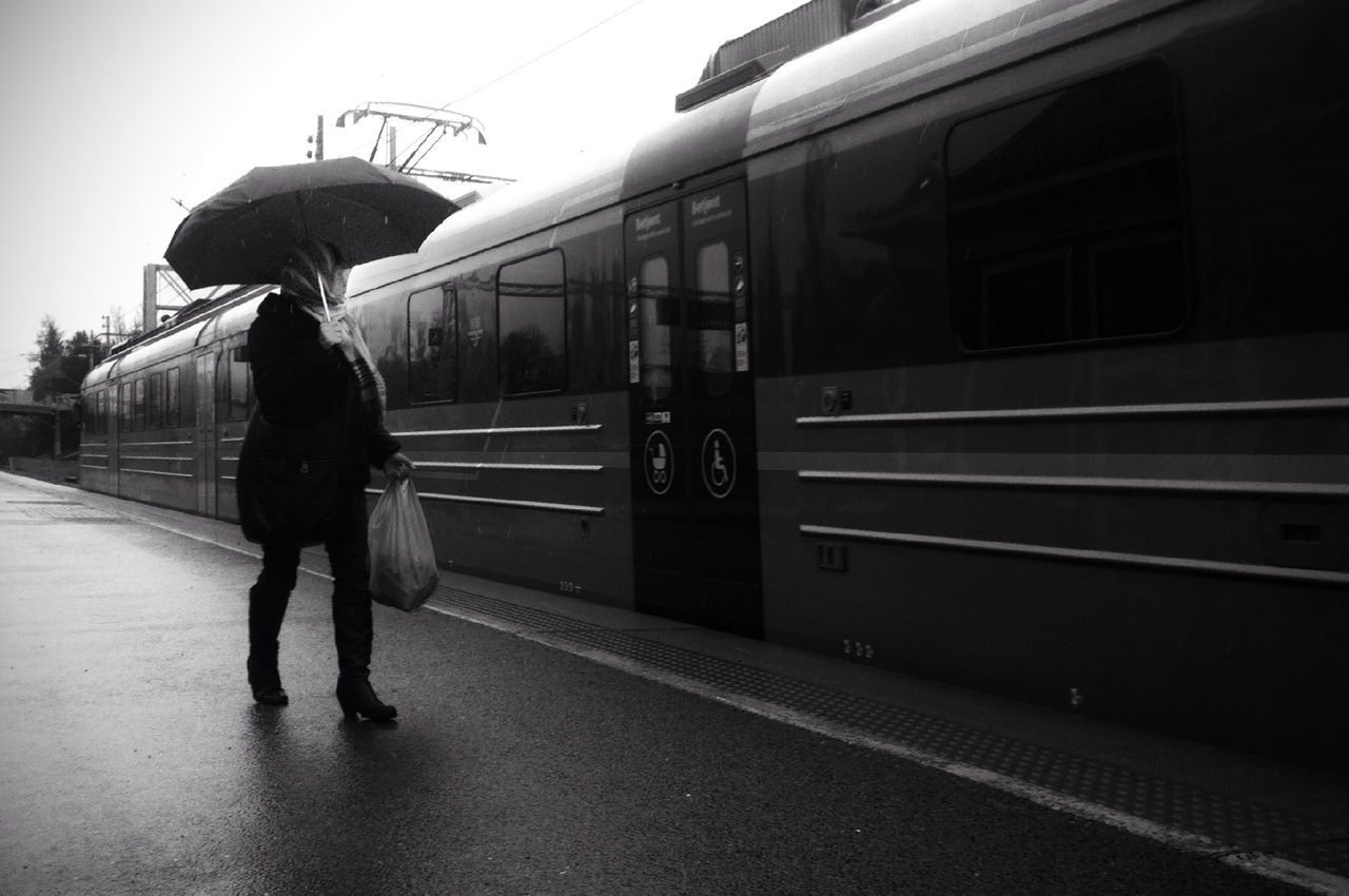 Woman carrying umbrella looking at train