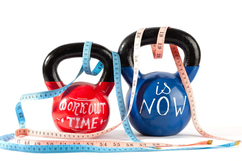 Red and blue kettlebells with Workout time is now lettering and measuring tape isolated on white background - healthy lifestyle and weight loss concept Measuring Tape Weight Loss Blue Capital Letter Close-up Communication Concept Conceptual Copy Space Cut Out Healthy Lifestyle Indoors  Kettle Bells Lettering No People Number Red Sport Sports Equipment Still Life Studio Shot Tape Measure Text Time Western Script White Background Workout Time