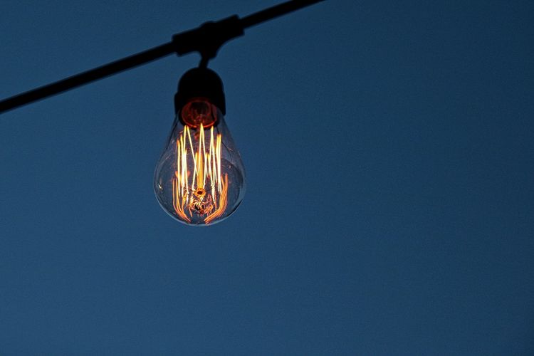 Low angle view of illuminated light bulb against clear blue sky