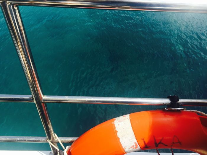 Life belt on railing of boat against sea