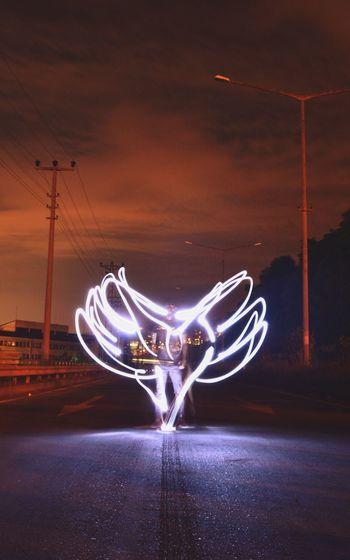 Digital composite image of illuminated light against sky at night