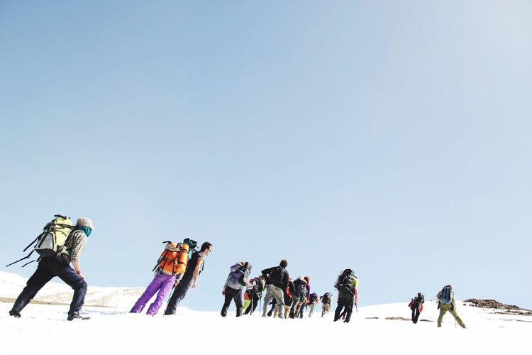 Group Of People With Backpacks Standing On Snowcapped Mountain Against Sky