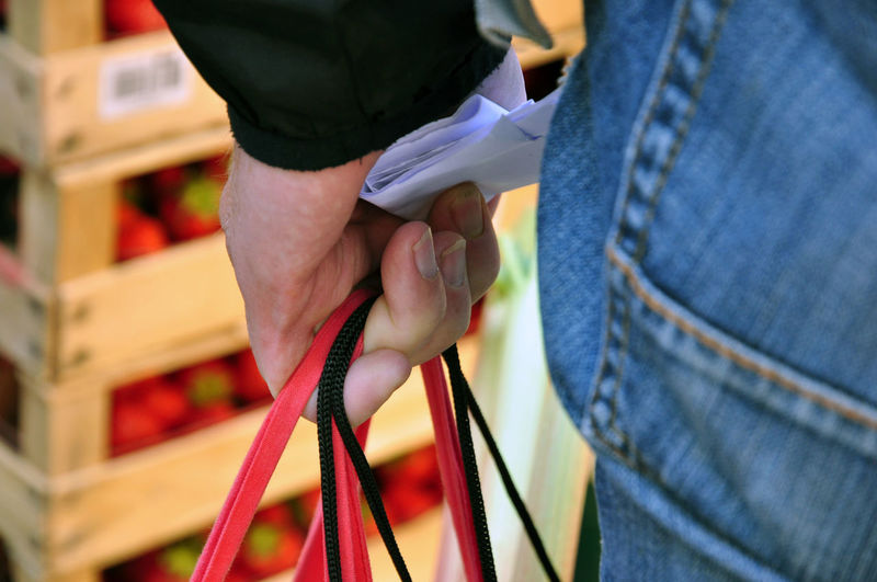 Midsection of man holding shopping bags