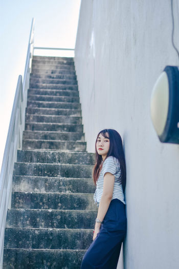 Portrait of young woman standing by wall on stairs at building terrace