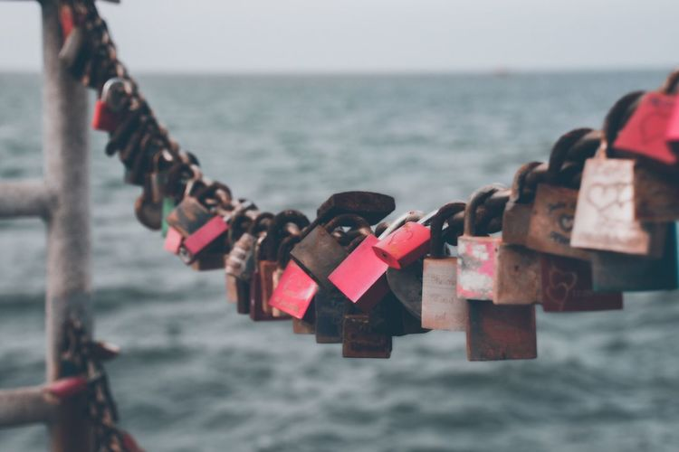 Love locks hanging on chain against sea and sky