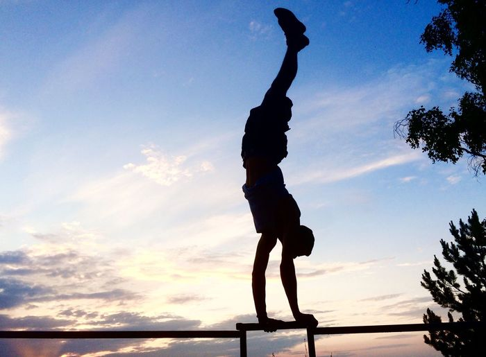Man doing handstand on bar