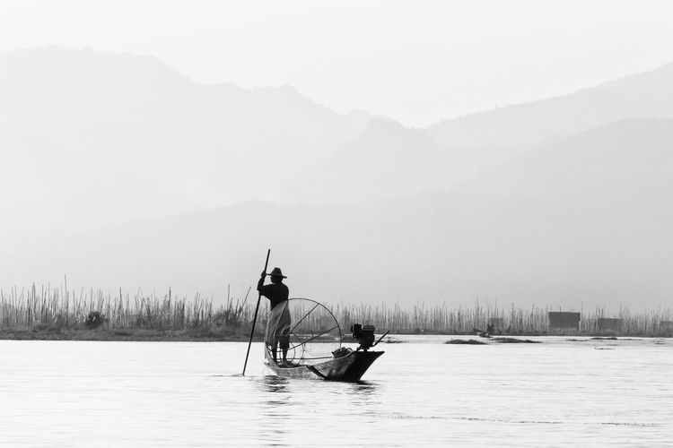 Fisherman standing on boat in lake against sky