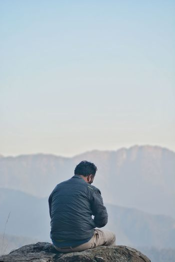 Rear view of man looking at mountain against sky