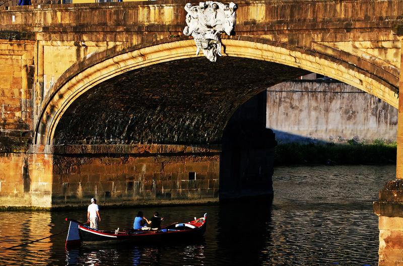 Tourists Riding In Boat On Arno River Under Ponte Santa Trinita