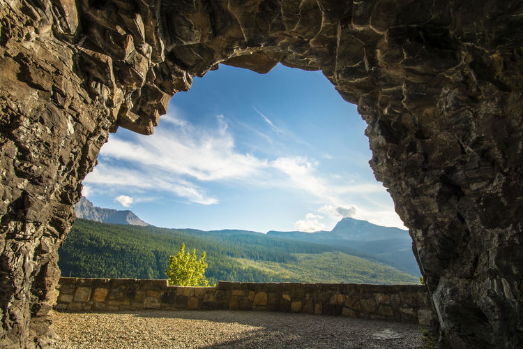 Scenic view of mountains against sky seen through cave
