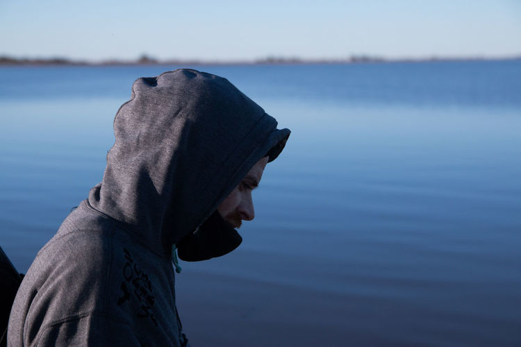 Man with hooded jacket near the sea