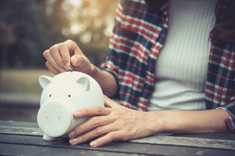 Midsection Of Woman Putting Coin In Piggy Bank