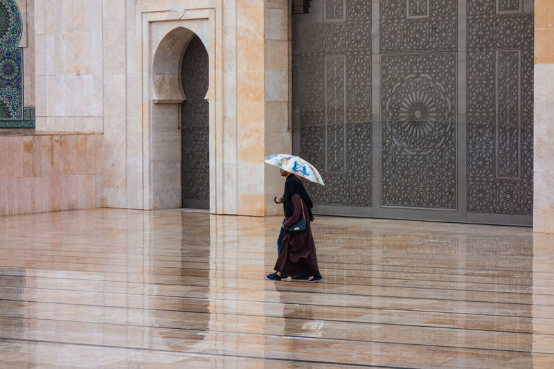 Couple with umbrella walkibg in hassan ii mosque square in a rainy day