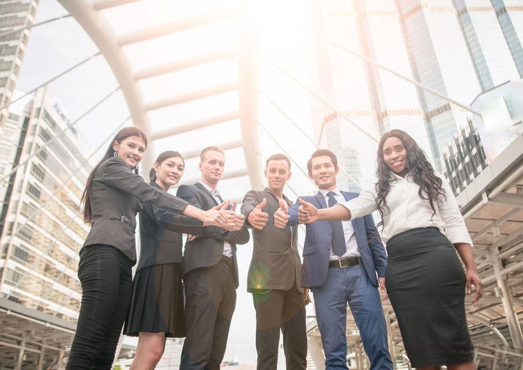 Low Angle Portrait Of Confident Business Colleagues Gesturing Thumbs Up While Standing In City