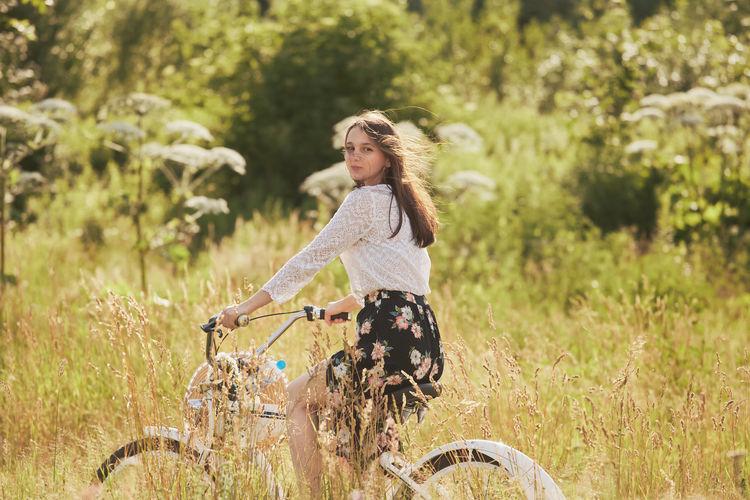 Happy brunette girl cyclist biking at sunny meadow